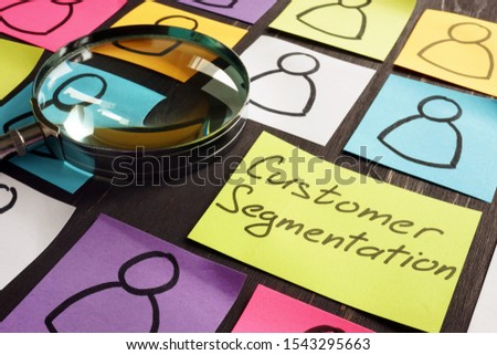 Customer Segmentation marketing concept. Magnifying glass and papers.