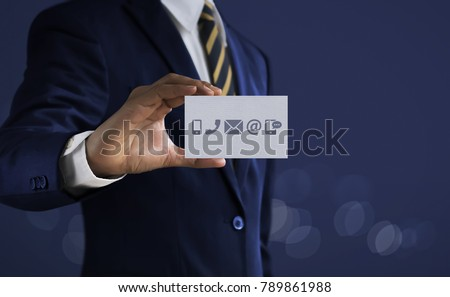 Shutterstock Customer service, call center service or contact us concept Businessman holding communication icons (mobile phone, telephone, mail, email, social media) card on dark tone background.