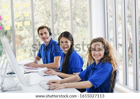 customer service center staff happy smile with office headset,call center and provide after sale information,with team of staff,helping answer call and telephone marketing,concept business and service