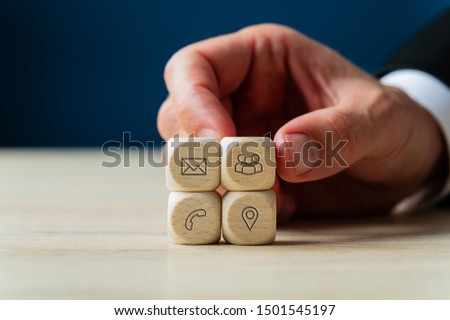 Customer service concept with businessman stacking wooden dices with contact information icons on them.  #1501545197