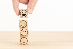 Customer service evaluation and satisfaction survey concept. Hand picked the happy face emoticon on wooden blocks. Copy space