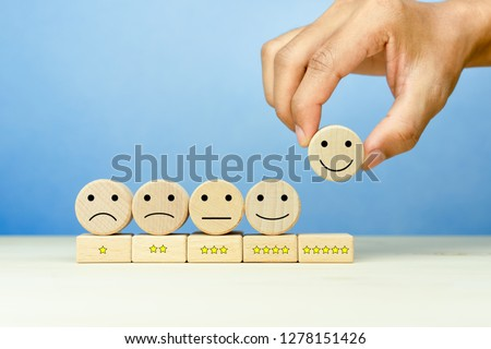Customer service evaluation and satisfaction survey concepts. The client's hand picked the happy face smile face icon and five star symbol on wooden cube on table
