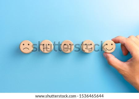 Customer service evaluation and satisfaction survey concepts. The client's hand picked the happy face smile face icon on wooden cube on blue background. copy space Stockfoto ©