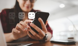 Customer service evaluation concept. smiling Asian female Is using a smartphone And she is pressing face emoticon smiling in satisfaction on virtual touch screen.