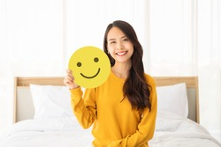 Customer service experience and business satisfaction survey. Asian woman holding paper with smiley face