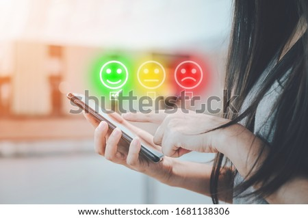 Customer service experience and business satisfaction survey. Close-up image of female hands using mobile smartphone choose face smile Foto stock ©