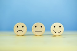 Customer service experience and satisfaction survey concept with facial expressions negative, neutral and positive on wooden cube on table, blue background, copy space