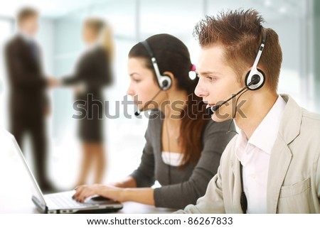 Customer service representatives in modern office with  headsets. Business people shaking hands on background
