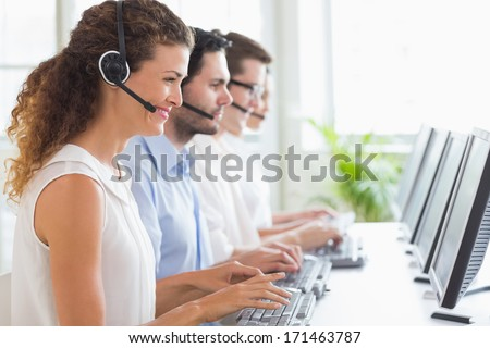 Customer service representatives working at desk in office