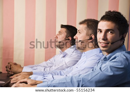 Customer service team with men in office,first man facing you and smiling