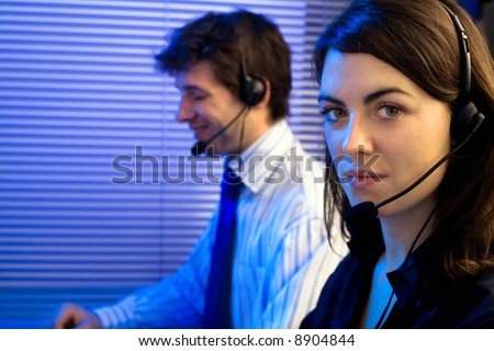 Customer service team working in headsets, late night at office. Focus placed on woman in front.