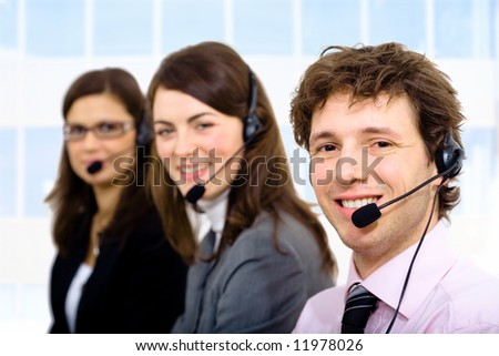 Customer service team working in headsets, smiling. Man in front.