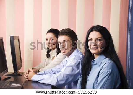 Customer service teamwork with two women and one man sitting on chair at desktop in office and smiling for you,vertical blinds background