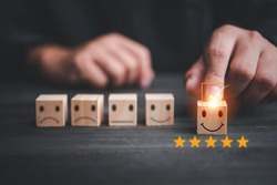 customer services best excellent business rating experience. Satisfaction survey concept. Hand of a businessman chooses a smiley face on wood block cube. 5 Star Satisfaction.