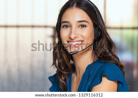 Customer support woman smiling and looking at camera. Portrait of happy customer support phone operator at call center wearing headset. Cheerful executive at your service working at office.