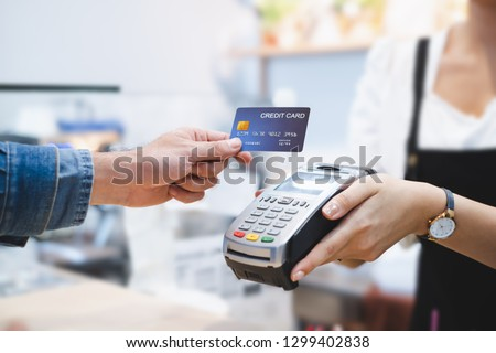 Photo of  Customer using credit card for payment to owner at cafe restaurant, cashless technology and credit card payment concept