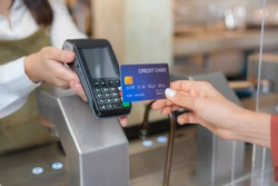 Customer using dummy credit card for purchase to waitress without touching EDC at cashier in cafe restaurant to keep distancing during COVID pandemic. Cashless, technology, wireless payment concept.