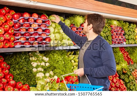 Customer with shopping basket buys vegetables in the vegetable department in the supermarket