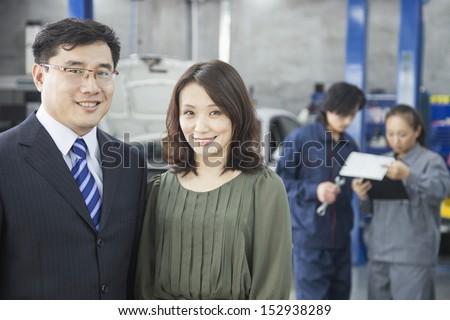 Customers and Mechanics in Auto Repair Shop
