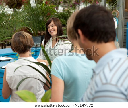Customers at check-out counter in garden center - stock photo