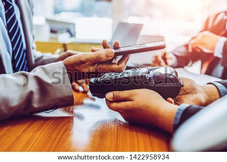 Customers paying bill financial quick cash by NFC payment pos technology with mobile app in smartphone, asian people. #1422958934