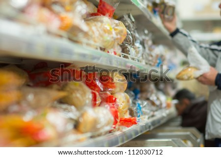 Customers select variety of bread on shelves in supermarket