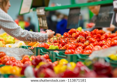 Customers selecting tomatoes in supermarket