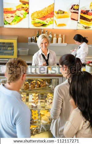 Customers waiting in line to buy dessert woman man cafe
