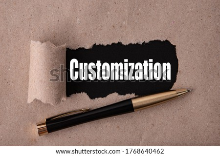 CUSTOMIZATION text written under torn paper and a recumbent metal pen. Business strategy concepts. Foto stock ©