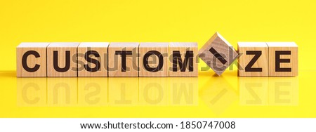 customize word written on wood block. customize word is made of wooden building blocks lying on the yellow table. customize, business concept, yellow background Stock photo ©