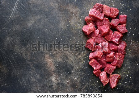 Cut beef with sea salt and dried herb on a dark metal or slate background.Top view with copy space.