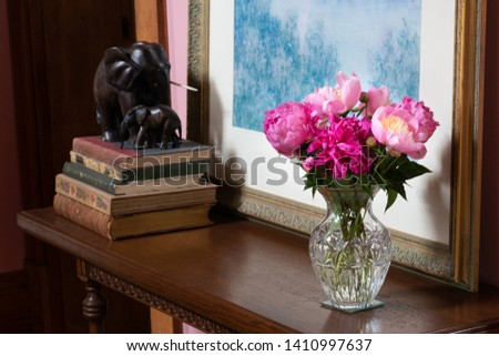 Cut crystal vase with peonies on antique table with framed Pastel, antique books and ebony carved elephants.