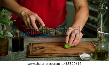 Cut cucumber. A female vegetarian is preparing a vegetarian vegetable salad.