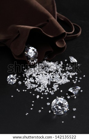 cut diamonds on shiny black surface close up. more diamonds out of focus in background