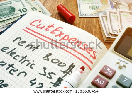 Cut Expenses for monthly home budget. Note pad and calculator. #1383630464