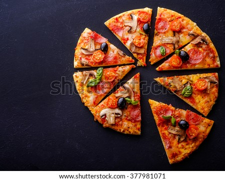 Cut into slices delicious fresh pizza with mushrooms and pepperoni on a dark background. Top view. Copyspace.