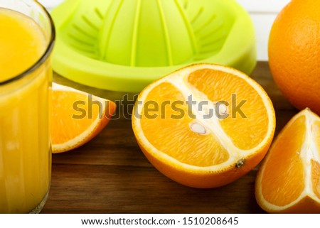 cut juicy fresh orange and a glass of freshly squeezed juice on a wooden background. place for text