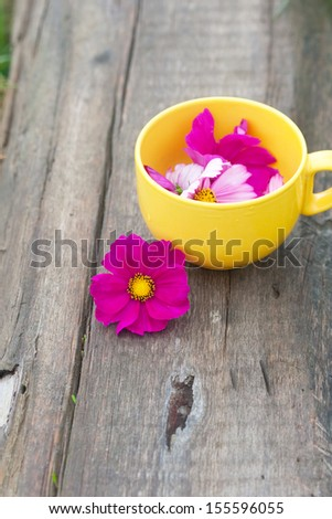 cut lilac flowers in the yellow mug on the wood board
