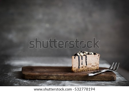Cut of raw chocolate mousse cake with cashew, hazelnuts and dark chocolate glaze topping on a wooden and grey background. Vegan sugar gluten free dessert. Dark food photography. Copy space, horizontal