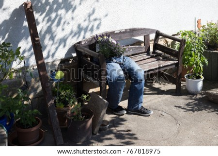 cut-off jeans decorated with flowers sitting on a garden bench as outdoor decoration in south germany countryside on a summer day in july #767818975