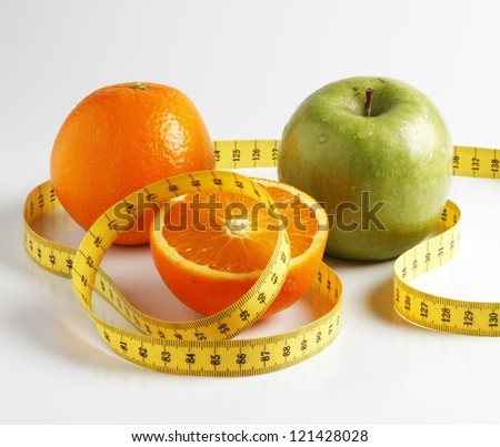 Cut orange and green apple with yellow measure tape