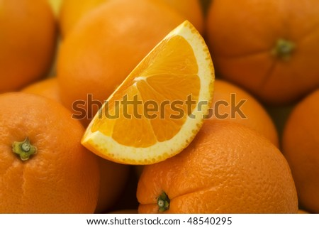 Cut Orange Quarter sitting on a pile of Oranges