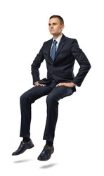 Cut-out full portrait of a businessman sitting on an invisible surface. Confident pose. Determination and perseverance. Confidence in the correctness of its decision. Reliable support.