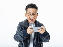 Cut out portrait of smart young Asian boy wearing glasses and casual black jacket exciting and happily laugh as enjoy playing attractive funny game and interesting info on favorite mobile phone