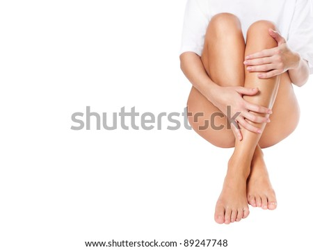 cut out slender naked female legs being massaged isolated on white - healthcare and beauty concept