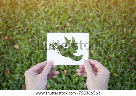 Cut paper with the logo of bird ( pigeon, dove ) over green grass. Peace sign and symbol background banner template of peace concept