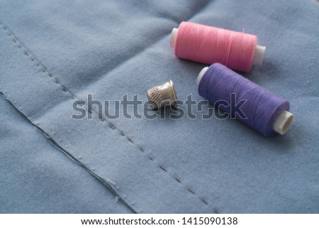 Cut part of skirt with a sewn tuck, thimble and two spools of thread. Two spools of pink and purple threads and tailor tool are lying on the blue basting fabric #1415090138
