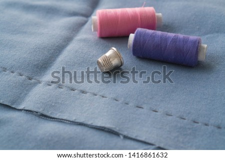 Cut part of skirt with a sewn tuck, thimble and two spools of thread. Two spools of pink and purple threads and tailor tool are lying on the blue basting fabric #1416861632