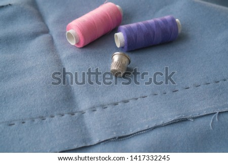 Cut part of skirt with a sewn tuck, thimble and two spools of thread. Two spools of pink and purple threads and tailor tool are lying on the blue basting fabric #1417332245