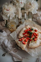cut piece of pavlova dessert on a vintage cake spoon top view. pavlova dessert with whipped cream, lemon curd, raw organic strawberries and mint leaf. meringue-based dessert with sliced strawberries